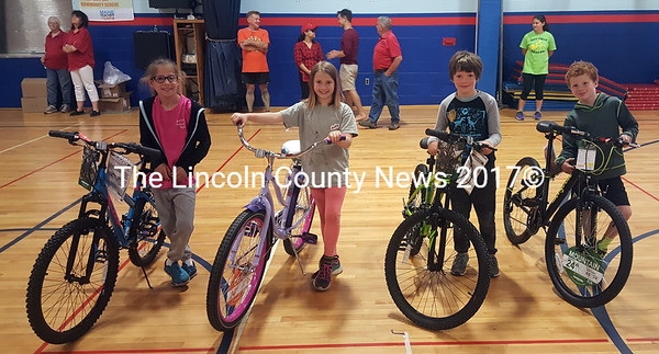 From left: winners Maggie Thompson, Brook McFarland, Atticus Donaghy, and Camden McCool stand beside their new bikes. (Remy Segovia photo)
