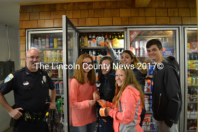 From left: Wiscasset School Resource Officer Craig Worster and volunteers Sarah Foley, Grace Webber, Maeve Blodgett, Vanessa Dunn, and Jesse Perkins place the last sticker at their first destination, Maxwell's Market. (Remy Segovia photo)
