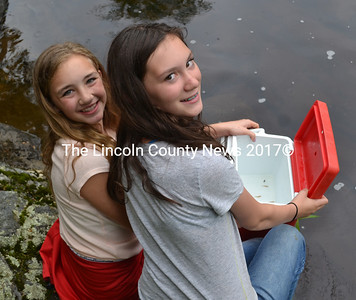 Wiscasset sixth-graders Hailey Acedo (left) and Acadia Kelley release a cooler full of Atlantic salmon fry into the Sheepscot River on Friday, June 16. (Abigail Adams photo)