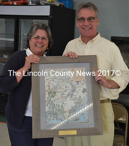 Damariscotta Board of Selectmen Chair Robin Mayer presents outgoing Selectman Jim Cosgrove with a framed Jake Day print for his years of service during the annual town meeting Wednesday, June 14. (Maia Zewert photo)