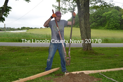 Volunteer Robert Colburn digs a hole for the fence. (Remy Segovia photo)