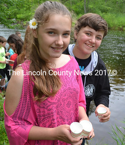 Sixth-graders Loralei Gilley (left) and Hallie Jackson hold cups with Atlantic salmon fry before releasing them into their native habitat. (Abigail Adams photo)