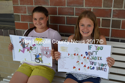 """Emory Shadis (left) and Annie Peaslee, both 11-year-old fifth-graders at Great Salt Bay Community School in Damariscotta, hold up the posters that netted them first and second place, respectively, in the Maine Academy of Family Physicians' staewide """"Tar Wars"""" poster contest. (Christine LaPado-Breglia photo)"""