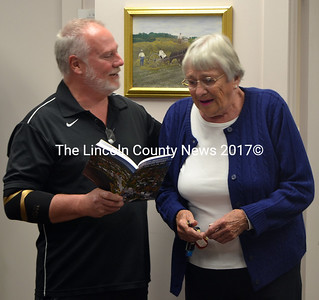 Newcastle Board of Selectmen Chair Brian Foote presents the town's annual report to an emotional Edna Verney. (Remy Segovia photo)