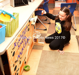 Jefferson Village School fourth grader Kimberly Walker demonstrates how her 'The Dog Feeder' machine works. Students in Mrs. Cunningham's class studied Rube Goldberg simple machines, then designed their own. (Paula Roberts photo)