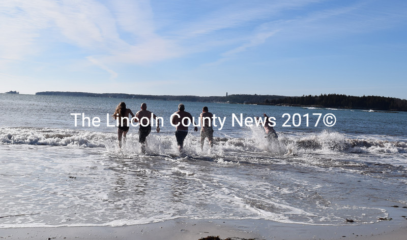 A small crowd of polar dippers splashes into the water off Pemaquid Beach on Sunday, Jan. 14. (J.W. Oliver photo)