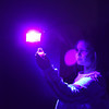 """Agnes Eddyblouin, 5, holds her """"nebula in a jar"""" up to a black light to watch it glow during Skidompha Library's """"A Wrinkle in Time"""" event Saturday, March 17. (Jessica Picard photo)"""