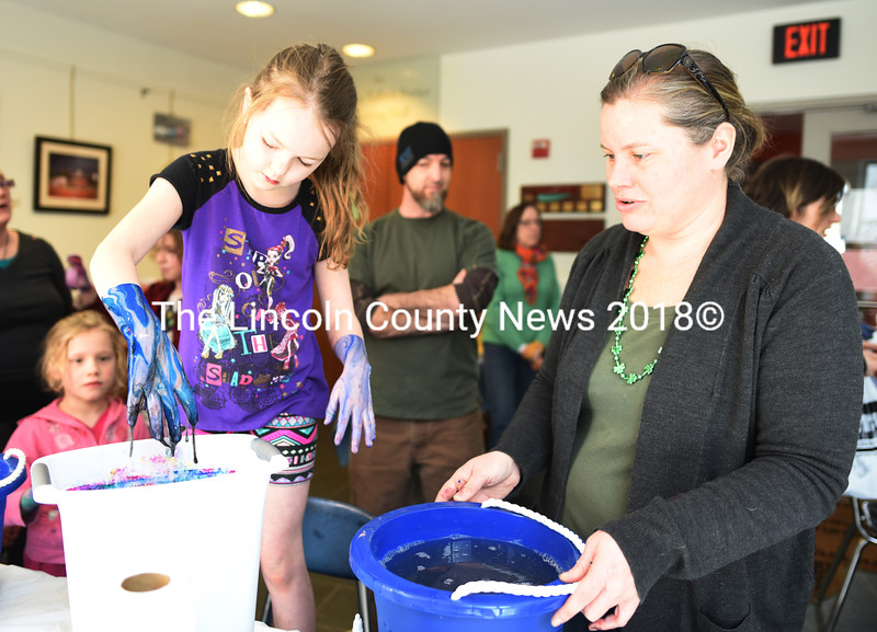 """October Brown, 7, marble paints her hands with the help of Erica Qualey during Skidompha Library's """"A Wrinkle in Time"""" event Saturday, March 17. (Jessica Picard photo)"""