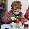 """Sawyer Piercy, 5, makes a """"nebula in a jar"""" by mixing glitter, glowsticks, and water during Skidompha Library's """"A Wrinkle in Time"""" event Saturday, March 17. (Jessica Picard photo)"""