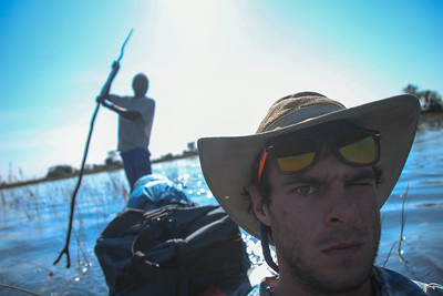 """Gregg Treinish takes a break from poling to take some photos from the front of the boat.  """"Snaps"""" is behind him poling the mokoro."""