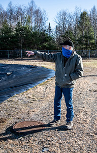 John Fancy points out the aeration system in the treatment lagoon in Waldoboro on Dec. 3. The cover near his feet is where Waldoboro's sewer lines ultimately converge to disperse the town's waste into the facility. (Bisi Cameron Yee photo)