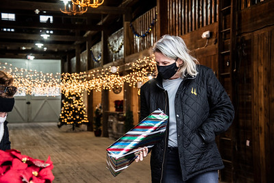 """Rose Fealy drops off a gift at Le Barn in Jefferson on Saturday, Dec. 12. Fealy had already brought gifts the previous weekend, but """"decided to come and deliver one more."""" (Bisi Cameron Yee photo)"""