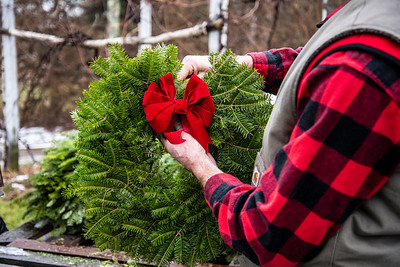 David Karas fastens a bow to a wreath in Waldoboro on Sunday, Dec. 13. Echo Hill Nursery's primary income comes from wreath sales. (Bisi Cameron Yee photo)
