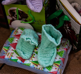 Baby booties hand-knitted by Aloisia Pollock wait under a tree at Le Barn in Jefferson on Saturday, Dec. 12. Pollock, along with a group of knitters from nearby Whitefield, crafted booties, hats, gloves, and baby blankets for donation to the Jefferson Area Community Food Pantry. (Bisi Cameron Yee photo)