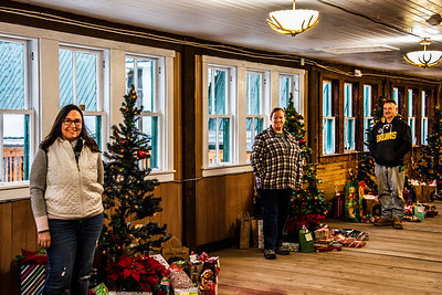 From left: Allison Brooks, Aaron Greene-Morse, and Scott Brooks stand in a line of Christmas trees at Le Barn in Jefferson on Saturday, Dec. 12. The three volunteers had come to collect the 242 gifts and $513 that had been donated to the pantry over the course of two weekends. (Bisi Cameron Yee photo)