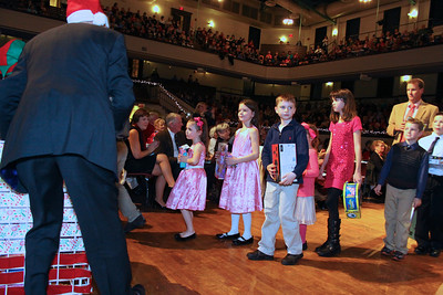 Children bring gifts to the Plymouth Area Coalition collection box at the the Phil Holiday Pops on Saturday night.