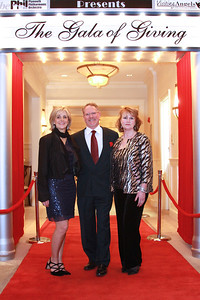 Plymouth Philharmonic Managing Director, Deb Cox, left, Visiting Angels Co-Managing Partner, Nate Murray, and Gala Committee Co-Chairman, Kathy Cogliano pose on the red carpet at the entrance to their organizations' collaborative  event, The Gala of Giving, held last Saturday evening at the Indian Pond Country Club  Proceeds from the fundraiser will benefit the Phil's Cultural Programs and the Special Needs Emergency Funds of the Old Colony and South Shore Elder Services.