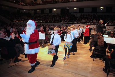 Santa leads a long line of children bearing gifts for the Children's Holiday Fund at the Phil's Holiday Pops concert.  The fund is sponsored by the Old Colony Memorial and administered by the Plymouth Area Coalition. Wicked Local Photo/Denise Maccaferri