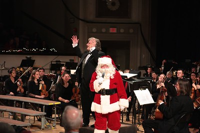 To the surprise of Phil Director Steven Karidoyanes, Santa takes over the microphone to chat with the audience. Wicked Local Photo/Denise Maccaferri