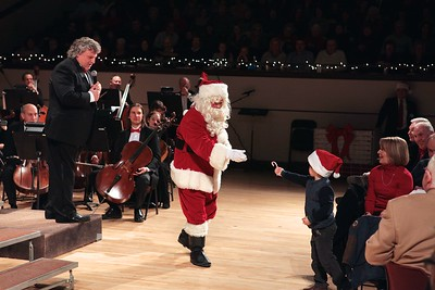A young boy comes forward from the audience to offer Santa a candy cane. Wicked Local Photo/Denise Maccaferri