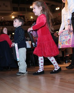 Two youngsters wait their turn to deposit gifts in the Children's Holiday Fund basket. Wicked Local Photo/Denise Maccaferri