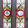Badly damaged window rebuilt and modified to include off-the-shelf bird roundels.
