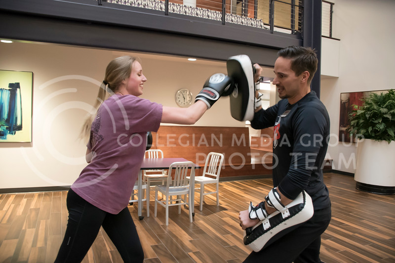 Tim Vettel, one of the owners of 9Round, runs a kickboxing drill with a Kansas State Student at the Stand Up For Your Sister fundraiser event in the Kansas State Student Union in Manhattan, KS, on Nov. 2, 2017. (Olivia Bergmeier | Collegian Media Group)