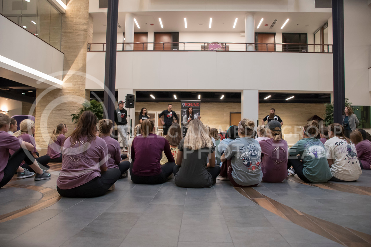 Kansas State Students listen to Melissa Vettel, one of the owners of 9Round, at the end of the kickboxing excersises at the Stand Up For Your Sister Fundraiser event in the Kansas State Student Union in Manhattan, KS, on Nov. 2, 2017. (Olivia Bergmeier | Collegian Media Group)