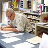 BEN GARVER — THE BERKSHIRE EAGLE<br /> George Aslan, owner of Candle Lanes in Pittsfield, keeps up with paperwork between customers.