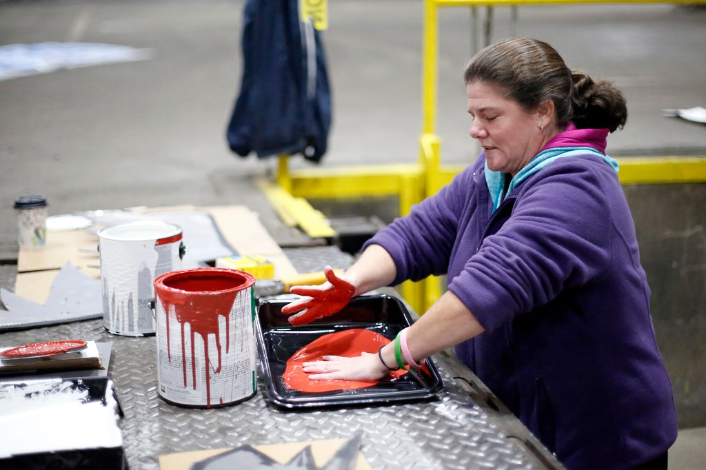 . Second grade teacher Mickie Turner \'bloodies\' her hands with red paint at a Neenah Technical Materials warehouse in Dalton where she and other volunteers from Conte Community School build their \'Haunted Hospital\' float for the annual Halloween Parade in Pittsfield. Wednesday, October 26, 2016. Stephanie Zollshan � The Berkshire Eagle | photos.berkshireeagle.com