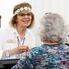 BEN GARVER — THE BERKSHIRE EAGLE<br /> Robin Florez of visitor services at the Norman Rockwell Museum in Stockbridge, greets a visitor in the spirit of Woodstock with a headband of daisys, Friday, August 16, 2019.