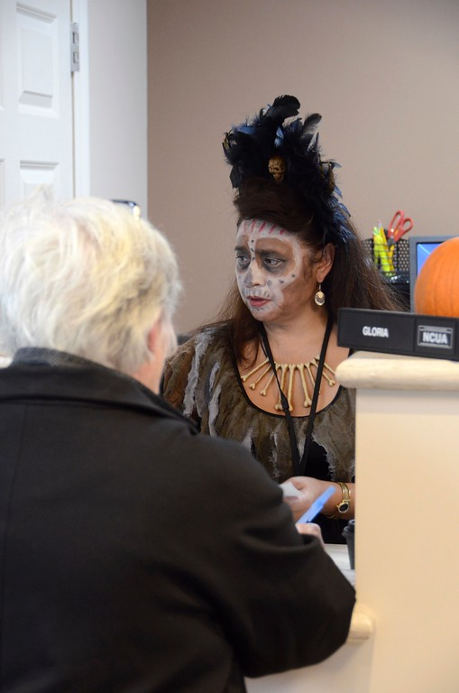 . Bank teller Gloria Escobar dresses as a voodoo queen for Halloween at the Lenox branch of the Greylock Federal Credit Union where employees dressed up for the holiday. Monday October 31, 2016. Gillian Jones � The Berkshire Eagle | photos.berkshireeagle.com