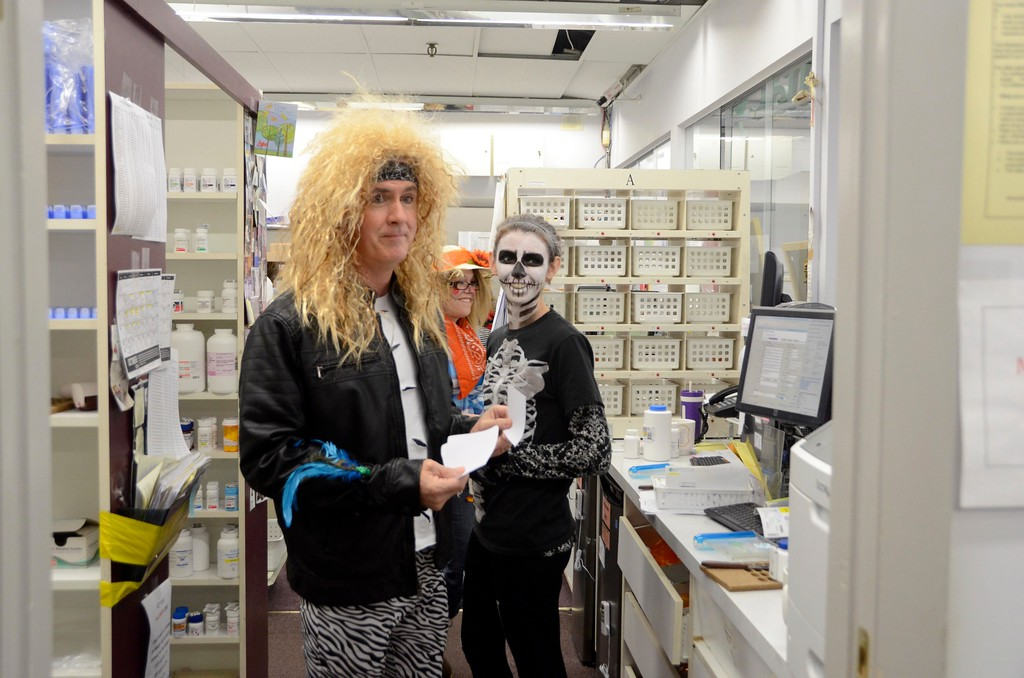 . Employees at Surgimed Littles HSC Pharmacy in North Adams dress up for Halloween nearly every year. Working in the pharmacy are from left, David Woods who is dressed up as an 80\'s rocker, Kyla Major as a skeleton and Rhianon Hayes as a scarecrow. Monday October 31, 2016. Gillian Jones � The Berkshire Eagle | photos.berkshireeagle.com