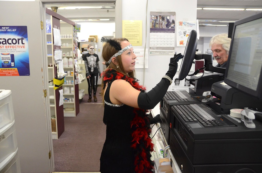 . Employees at Surgimed Littles HSC Pharmacy in North Adams dress up for Halloween nearly every year. Dressed as a 1920\'s flapper, Genevieve Tatro checks out a customer at the register while Kyla Major, dressed as a skeleton works in the pharmacy. Monday, October 31, 2016. Gillian Jones � The Berkshire Eagle | photos.berkshireeagle.com