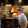 BEN GARVER — THE BERKSHIRE EAGLE<br /> Kevin Revels cooks sausage in the stone oven at M&M's Restaurant in New Lebanon.