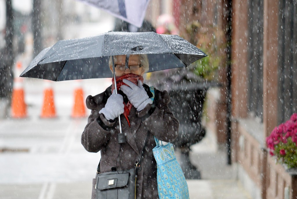 . Giselle Correa walks on North Street through some of the first snow of the season, Thursday, October 27, 2016. With temperatures hovering at just above freezing, the dusting of snow is not sticking yet.  Ben Garver, The Berkshire Eagle via AP