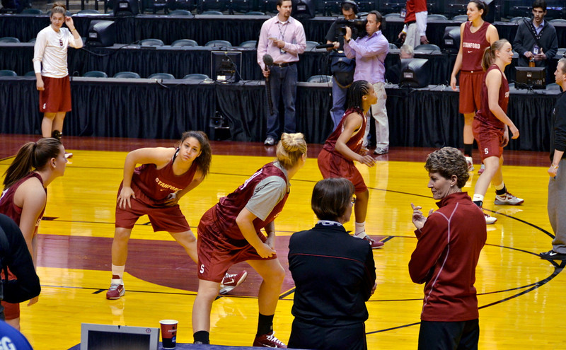 Tara and Amy consult while team stretches at start of open practice