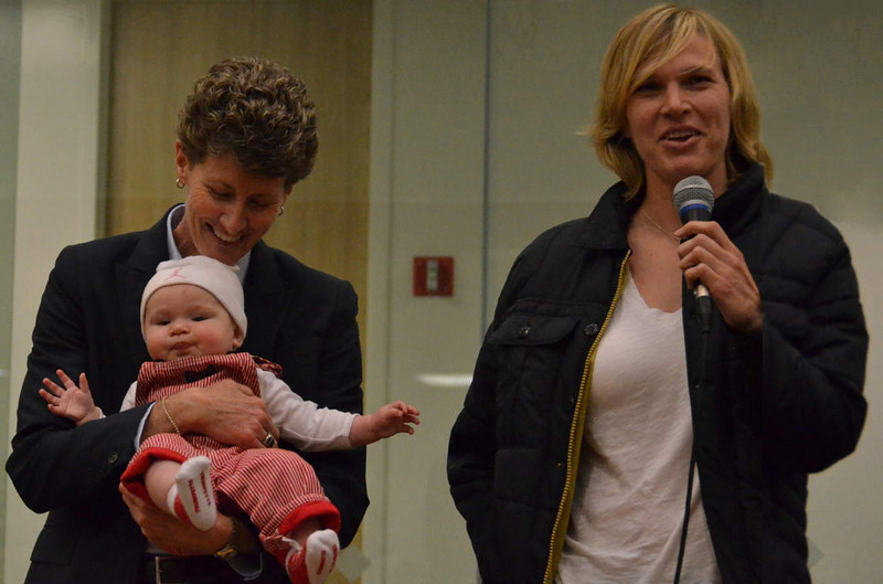 """At the post-game """"tent,"""" Coach Amy Tucker introduces Vanessa Nygaard and her 6-month-old daughter Emerson"""