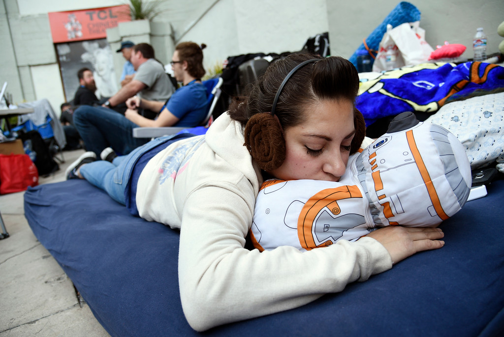 """. Lavonne Dominguez naps on an BB-8 pillow as she waits with other fans at the TCL Chinese Theatre for Thursday night\'s first screening of the film \""""Star Wars: The Last Jedi,\"""", on Tuesday, Dec. 12, 2017, in Los Angeles.  (AP Photo/Chris Pizzello)"""