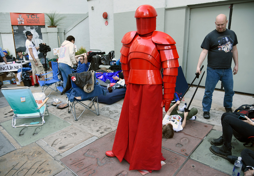""". A model of an Elite Praetorian Guard character from the upcoming film \""""Star Wars: The Last Jedi\"""" stands among fans waiting at the TCL Chinese Theatre on Tuesday, Dec. 12, 2017, for Thursday night\'s first screening of the film \""""Star Wars: The Last Jedi,\"""" in Los Angeles. At right in the photo are \""""Star Wars\"""" fans Richard Betel and his son Joseph 9, of Toronto, who have been waiting in line since Saturday night. (AP Photo/Chris Pizzello)"""