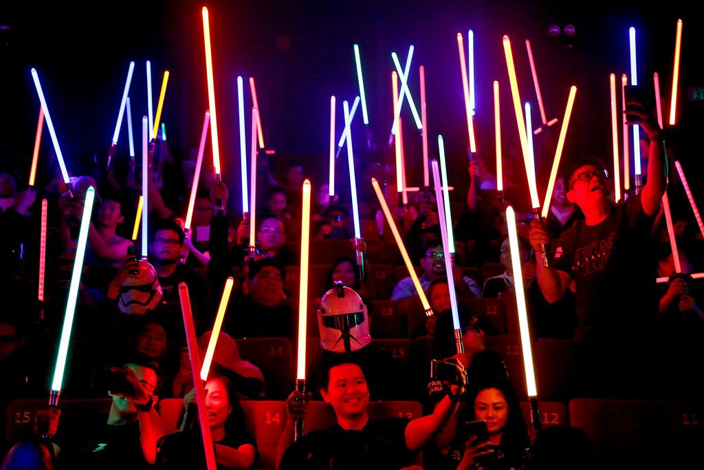 ". Star Wars fans raise their lightsabers before the starts of \""Star Wars: The Last Jedi\"" movie in Subang Jaya, Malaysia, Friday, Dec. 15, 2017. (AP Photo/Sadiq Asyraf)"