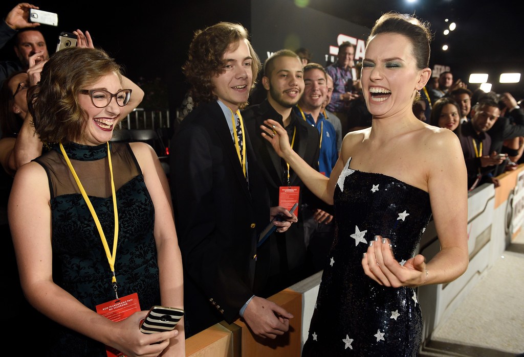 """. In this Dec. 9, 2017 photo, Daisy Ridley, right, a cast member in the film \""""Star Wars: The Last Jedi,\"""" laughs with Shannon McNabb, from left, Tyler Woodward and Chris Alegria at the premiere of the film at the Shrine Auditorium in Los Angeles. The teens were among seven teens with life-threatening medical conditions who were among the special guests at the premiere as part of the Make-A-Wish Foundation. (Photo by Chris Pizzello/Invision/AP)"""