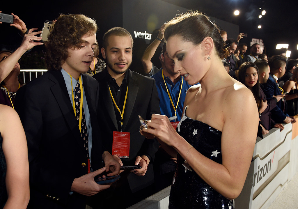 """. In this Dec. 9, 2017, photo, Daisy Ridley, right, a cast member in the film \""""Star Wars: The Last Jedi,\"""" signs an autograph as Tyler Woodward, 17, left, and Chris Alegria, 18, look on at the premiere of the film at the Shrine Auditorium in Los Angeles.  Woodward and Alegria were two of seven teens with life-threatening medical conditions who were among the special guests at the premiere as part of the Make-A-Wish Foundation. (Photo by Chris Pizzello/Invision/AP)"""