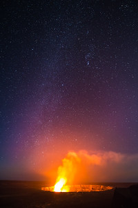 Molten lava at Halemaumau Crater in Volcanoes National Park in Hawaii produces a large orange glow against the Milky Way night sky.