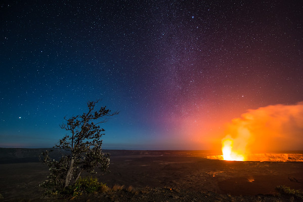 Molten lava at Halemaumau Crater in Volcanoes National Park in Hawaii produces a large orange glow against the Milky Way night sky and an Ohia tree.