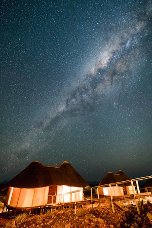 The Milky Way bright above a glowing bungalow in Namibia's Namib-Nakluft National Park.