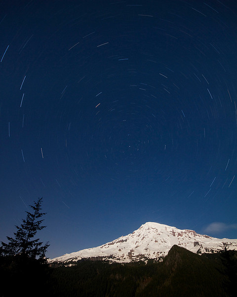 Stars spin by as Mount Rainier is lit by a full moon.