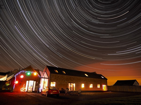 Star Trail over rural barn conversion during the festive Christmas period (with decorations).