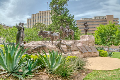 The Tejano Monument is a memorial at the State Capitol commemorating the impact of Tejanos on Texas culture and history. It features nine life-size bronze statues on a 275-ton Texas Sunset Red Granite base, and five plaques describing Tejano history.