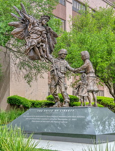 """""""The Price of Liberty"""" was unveiled on the grounds of the Texas State Capitol complex.  The memorial portrays a version of Lady Liberty taking a husband and father off to war while his tearful wife holds on. The couple's daughter also holds a U.S. flag which is folded into a triangle, symbolizing the loss of American loved ones who have passed in warfare."""